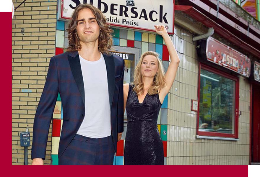 Langhaariger Mann in Anzug für Abschlussball von Brand-Moden Leidersbach und Frau in Abendkleid, festliche Anzüge Wiesbaden