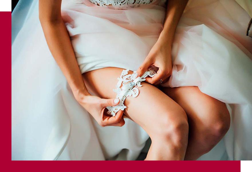 Braut im Hochzeitskleid legt sich Strumpfband an, Brand-Moden Leidersbach, Brautkleider Frankfurt